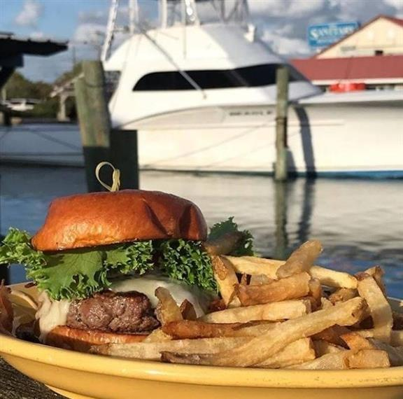 Burger and Fries plated on the outside deck in front of a boat in the background.