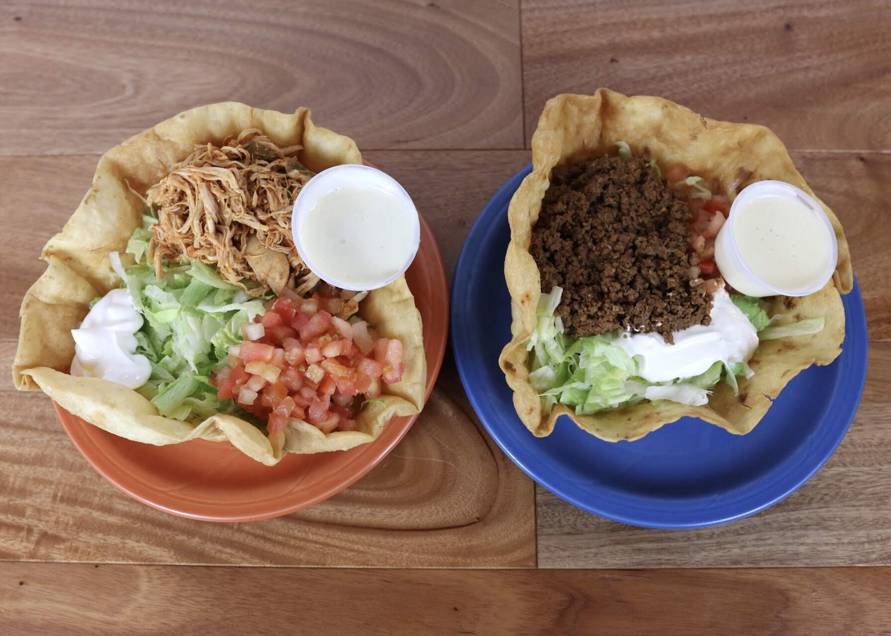 Two taco salad bowls side by side filled with pulled pork and beef with lettuce, tomatoes and sour cream