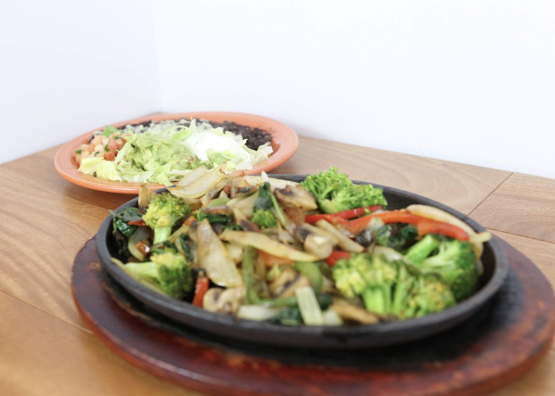 Mixed vegetable fajitas on a skillet with a side of lettuce, tomatoes, beans and rice