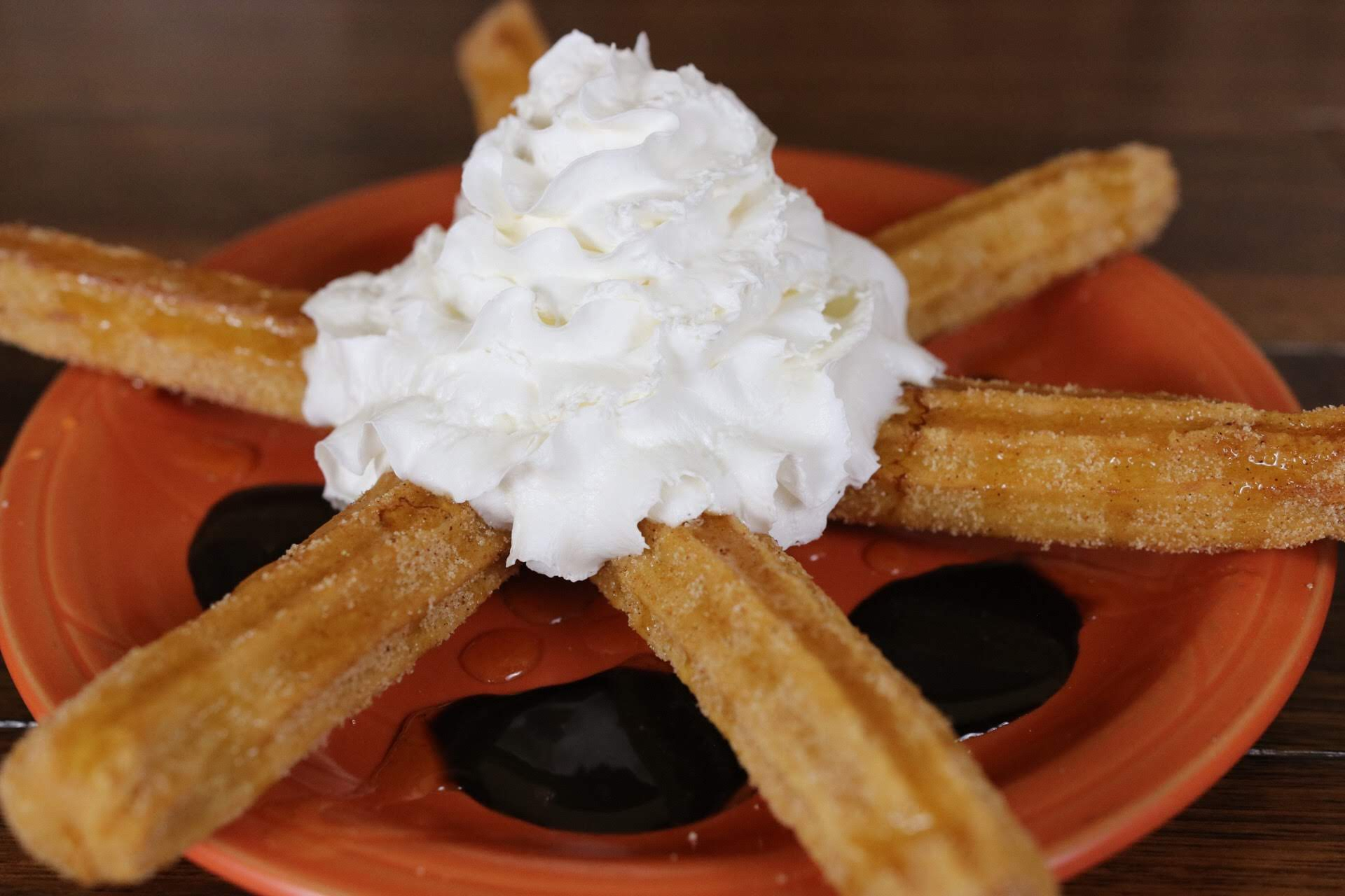Churros on a plate with whipped cream