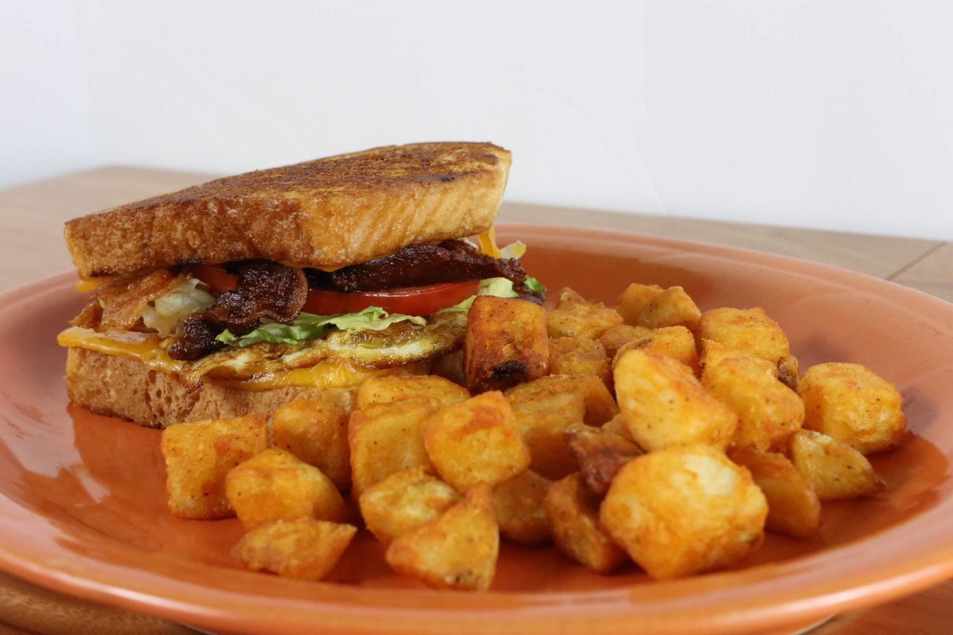Breakfast sandwich on Texas toast with breakfast potatoes