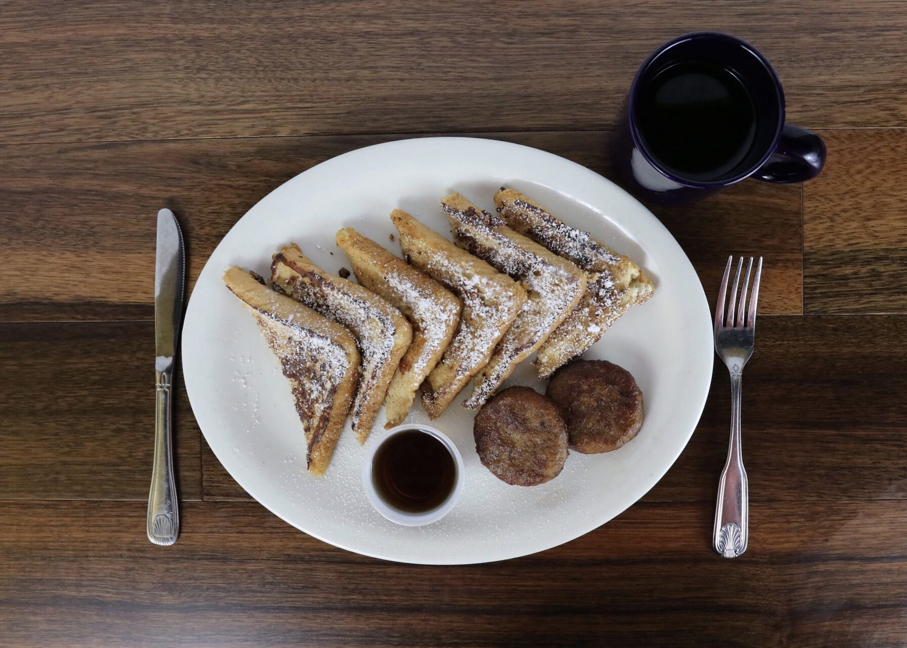Plate of French toast with maple syrup and a cup of coffee