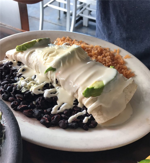 burrito with melted cheese, avocado, rice and beans