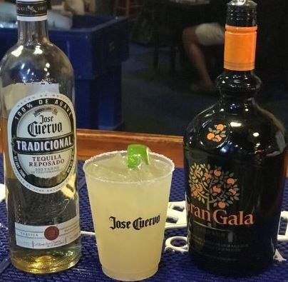 jose cuervo traditional tequila bottle on a bar with a margarita and a gran gala bottle