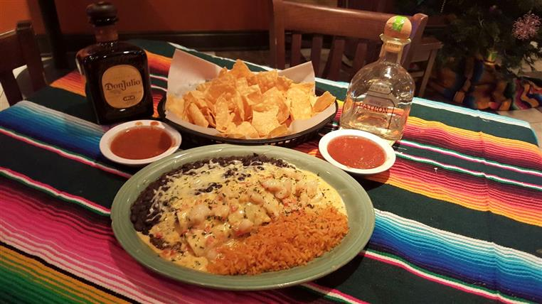 tequila bottles on a table with chicken enchiladas, rice and beans and chips and salsa