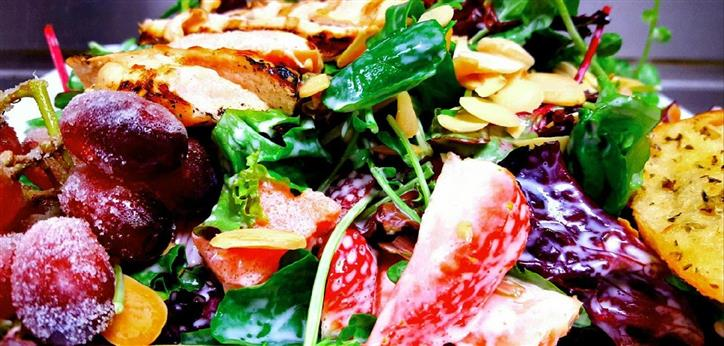 Melon berry salad. Sweet Creamy Sour Cream Dressing made with Strawberry Shrub, tossed with Spring Mix, Fresh Sliced Strawberries, Sliced Almonds, Watercrest, Diced Watermelon and garnished with Sugar Grapes.