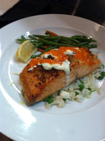 grilled salmon topped with sauce over rice with a side of green beans