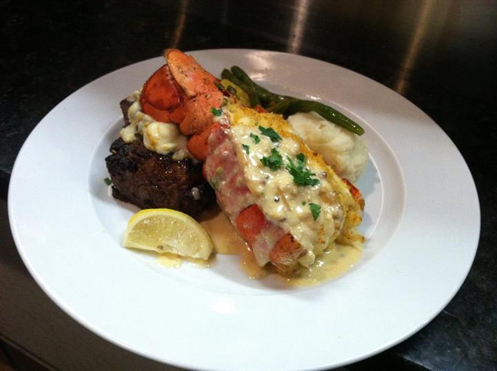 Steak and lobster tail over mashed potatoes and greens on dish.