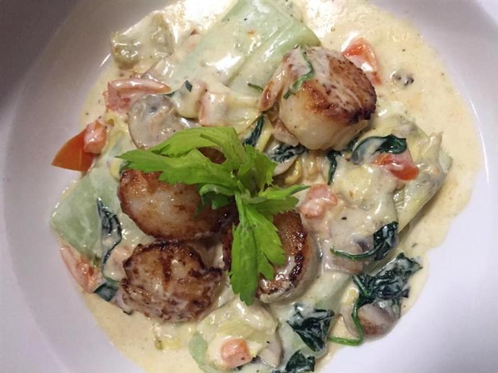 Scallops over fettuccine on dish