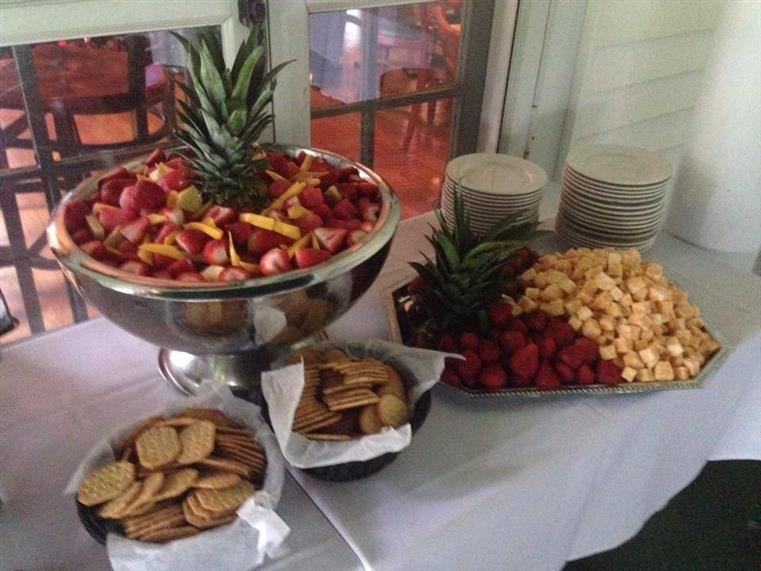 Fruit salad in large bowl, adjacent are bowls of crackers, strawberries and cheese tray, small white dishes on white-clothed table.