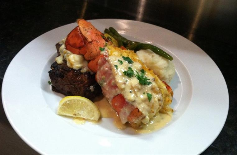 Steak and lobster tail over mashed potatoes and greens on white dish.
