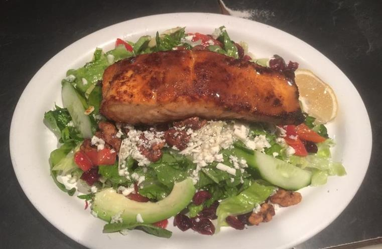 Salmon over cranberry walnut salad on white dish.