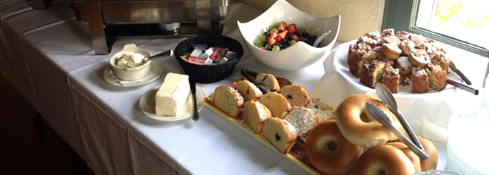 Bagels, muffins, fruit salad on clothed table next to butter and spreads.