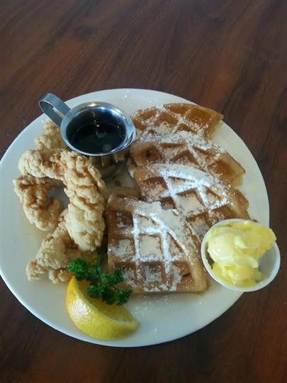 Chicken and waffles with powdered sugar and syrup
