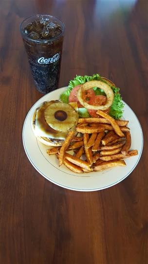 Cheeseburger with pineapple, onion ring, lettuce, and tomato with a side of fries
