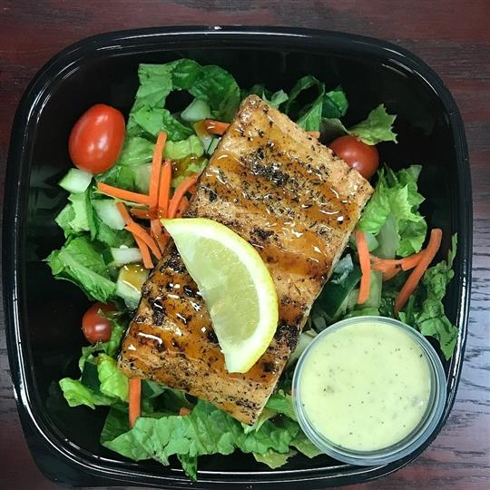 salad topped with grilled fish with dressing on the side