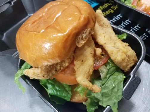 Fish stick sandwich, with lettuce and tomoato on a bun in a to go container