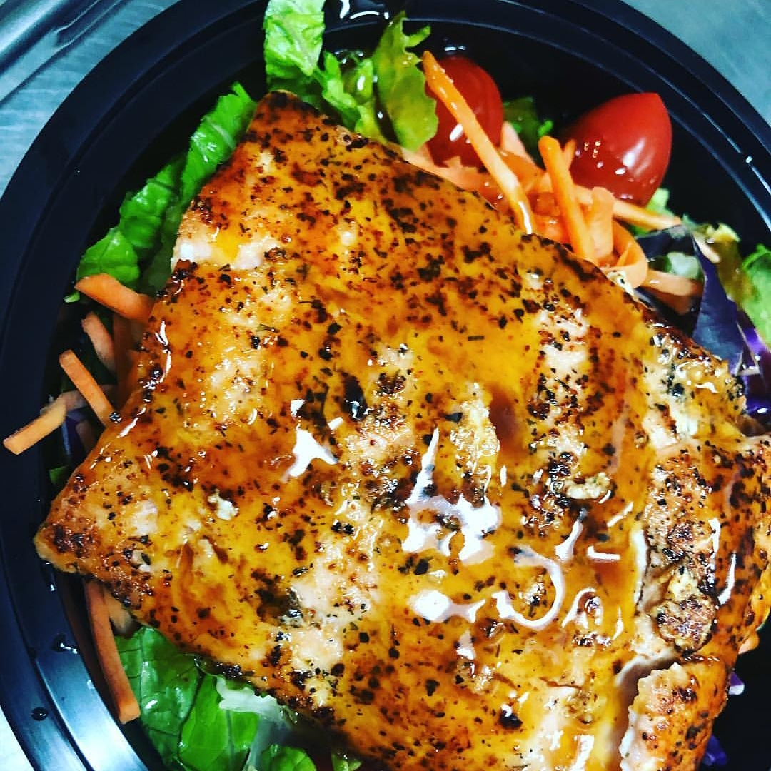 grilled seasoned fish on top of lettuce, carrots, onions and tomatoes in a togo container