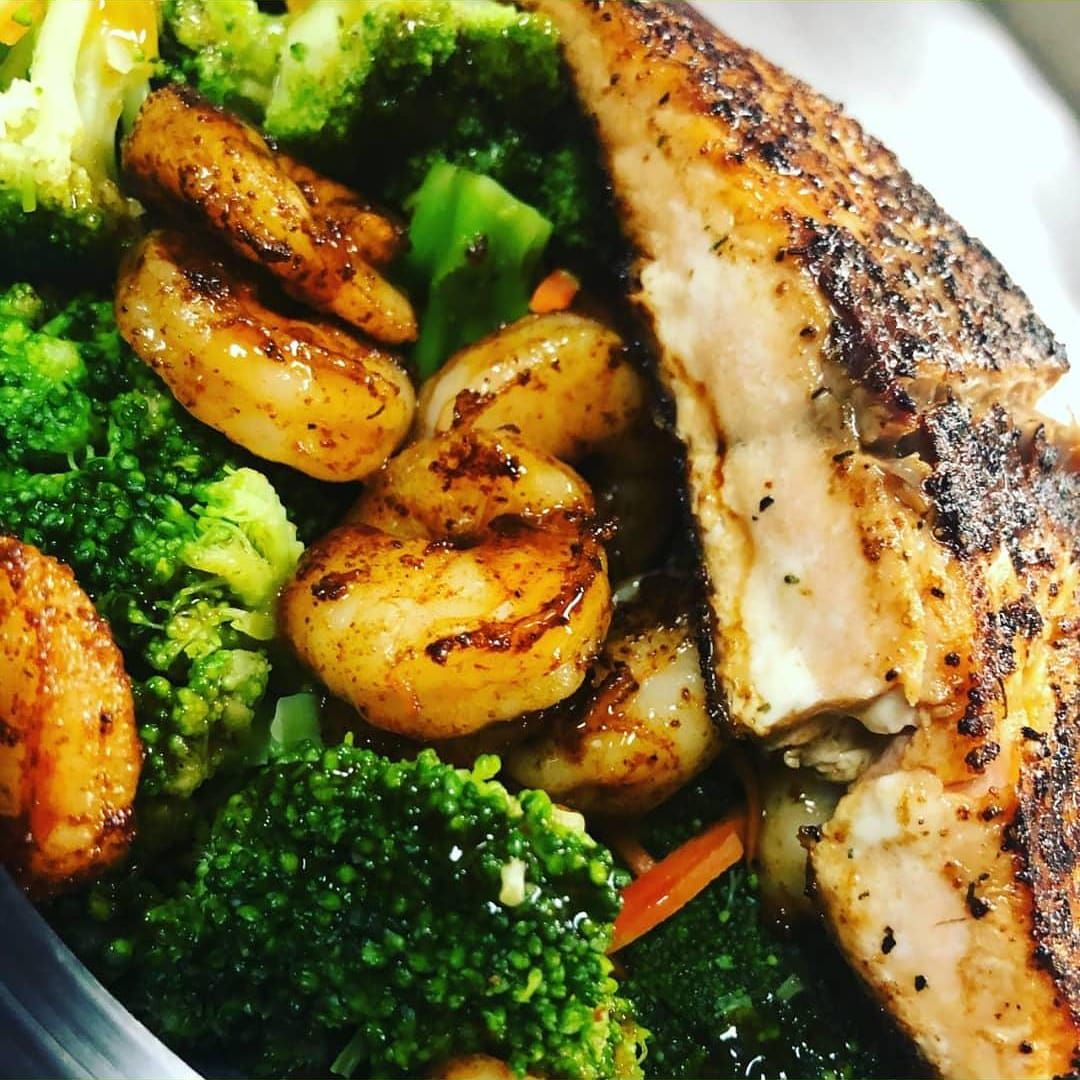 Grilled salmon with grilled shrimo on top of broccoli and carrots