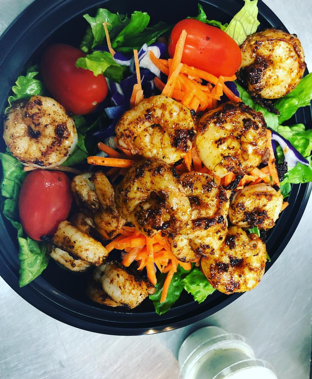 Grilled shrimp salad with lettuce cherry tomatoes, carrots and onions in a bowl