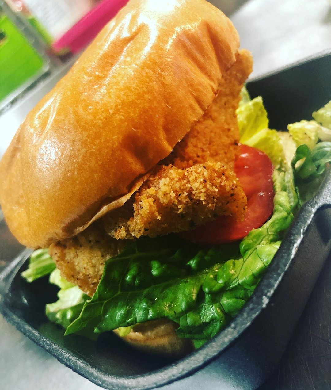fish sandwich with lettuce, tomatoe in a to go container