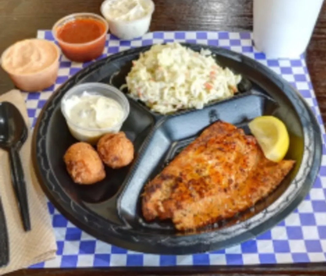 grilled salmon with lemon wedge, with a side of potato salad with cheese balls and dipping sauce