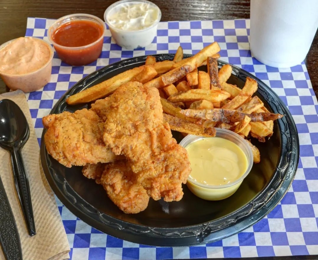 Fried fish on a plate with a side fries and 3 dipping sauces on a to go container