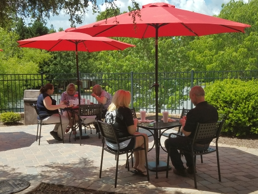 Two groups sitting at two different table outdoors