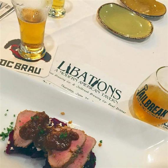 "A steak appetizer with glasses of beer on a table that says ""Libations, a modern American Tavern"""