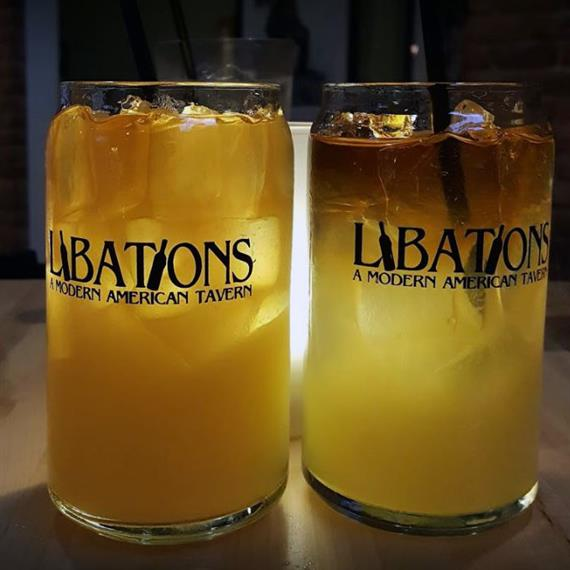 "2 mixed drinks in glass cups that say ""Libations a Modern American Tavern"""