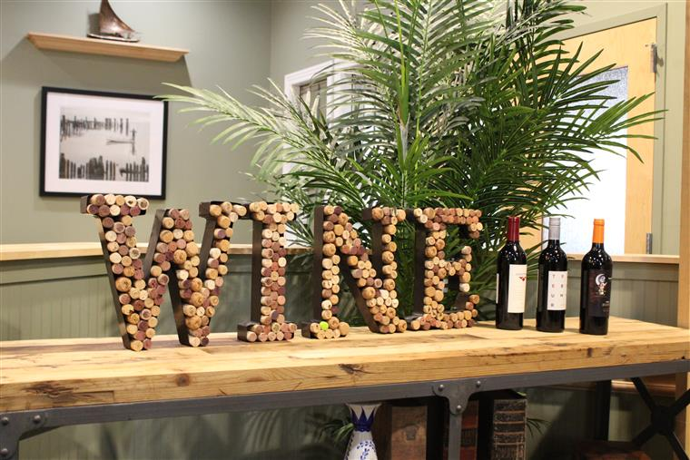 "The word ""Wine"" Spelled out using wine corks on a bar next to 3 bottles of wine"