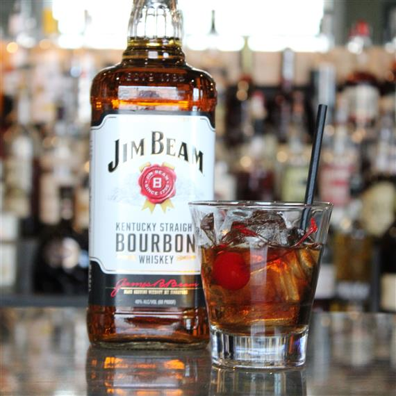 A Jim Bean Bourbon bottle on the bar with a glass of bourbon in front of it