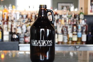 "A glass Jug Growler that says ""Libations a Modern American Tavern"""