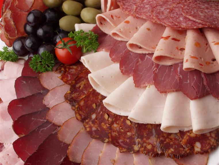 A cold cut platter display with cold cut meats such as turkey, salami, bologna, ham, etc.