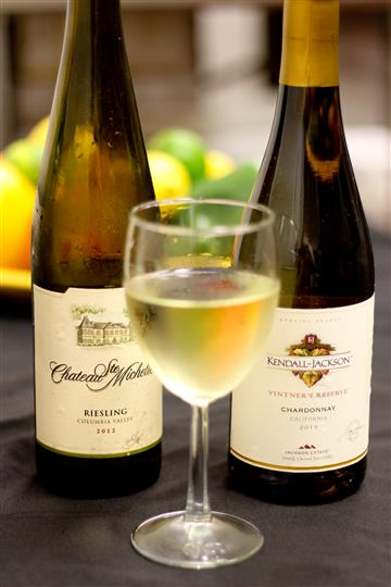2 White wine bottles and a glass of white wine
