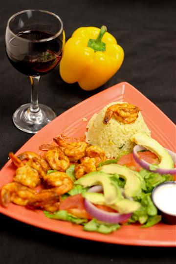 Shrimp with rice and salad topped with tomatoes, red onions, and avocados