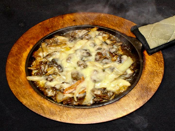 Steak, onions, mushrooms with melted cheese in skillet
