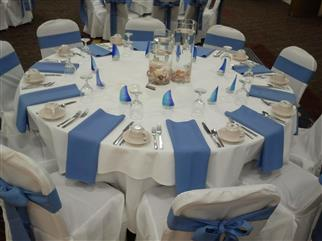 White tablecloth placesetting with napkins. White clothed chairs adorned with blue ribbon.