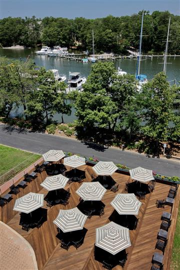 Tables on deck, covered with umbrellas with view of marina