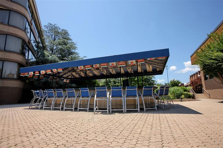 Canopy-covered outdoor bar surrounded by chairs next to hotel.