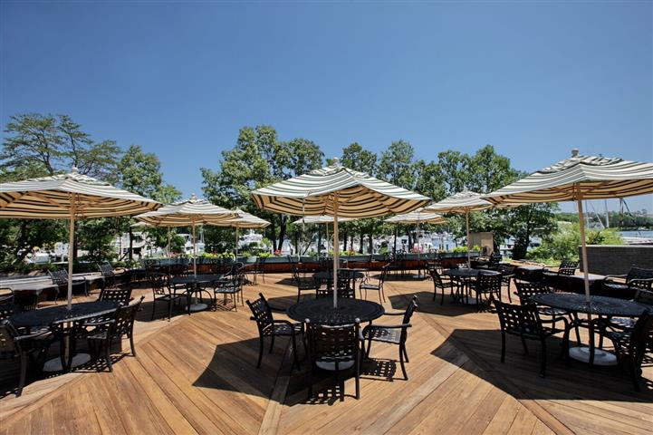 Umbrella covered tables and chairs outdoors on wooden deck