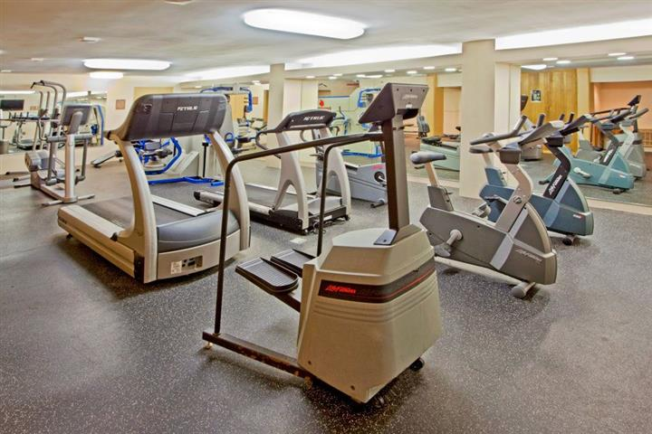 Exercise equipment in gym; treadmills and cycles