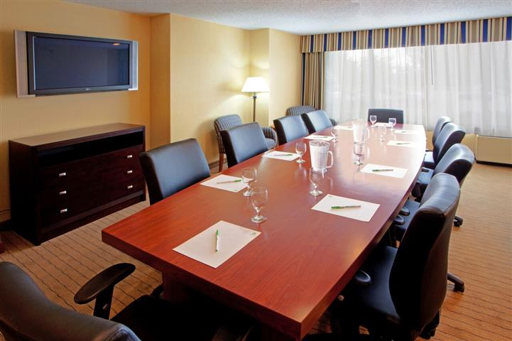 Conference room with leather chairs, wood table, television screen and large window.