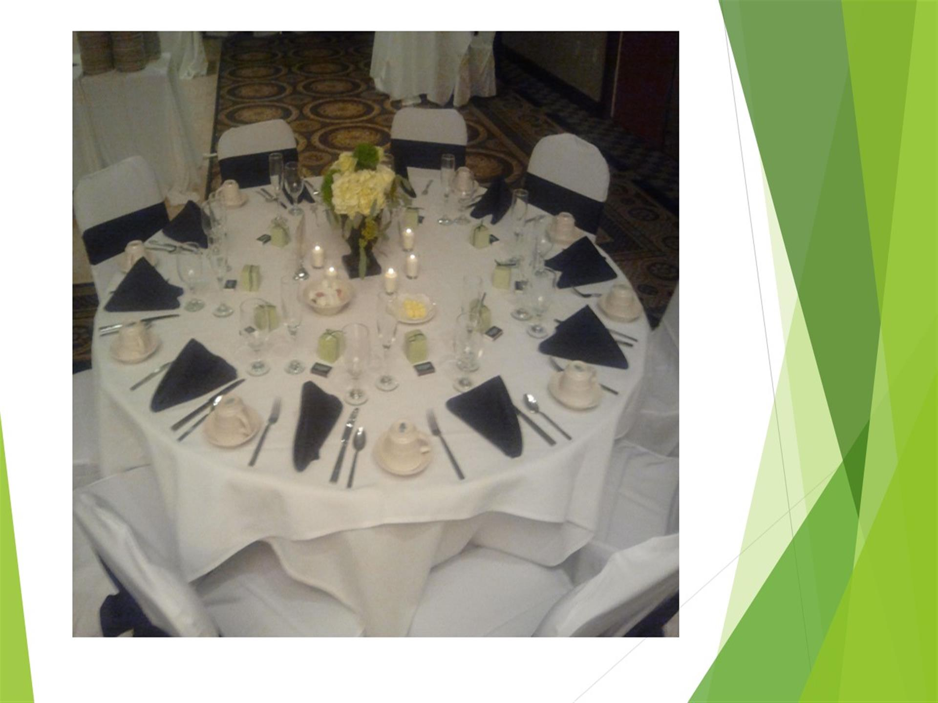 White tablecloth placesetting with blue napkins.
