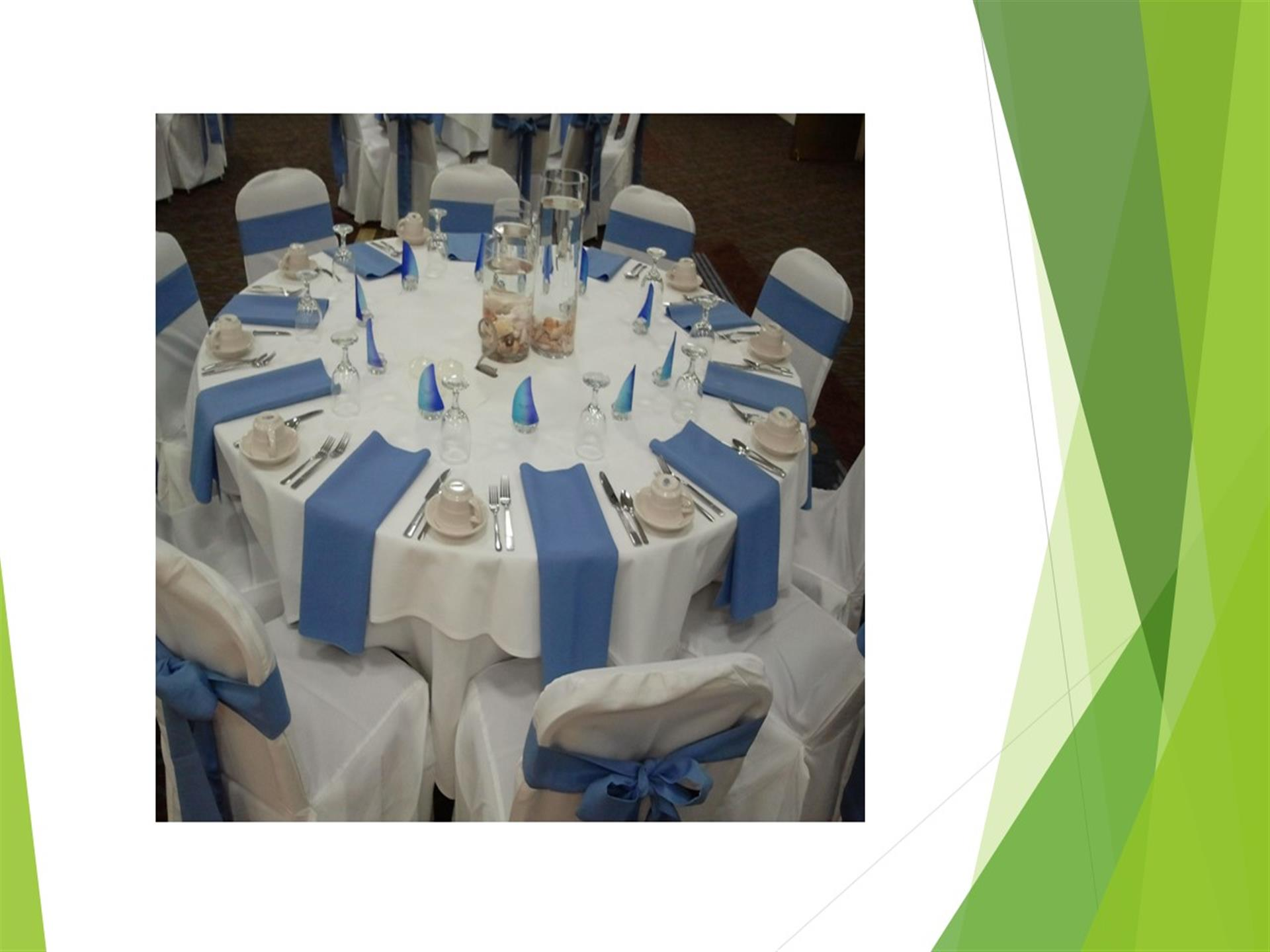 White tablecloth placesetting with blue napkins. White chairs adorned with blue ribbon.