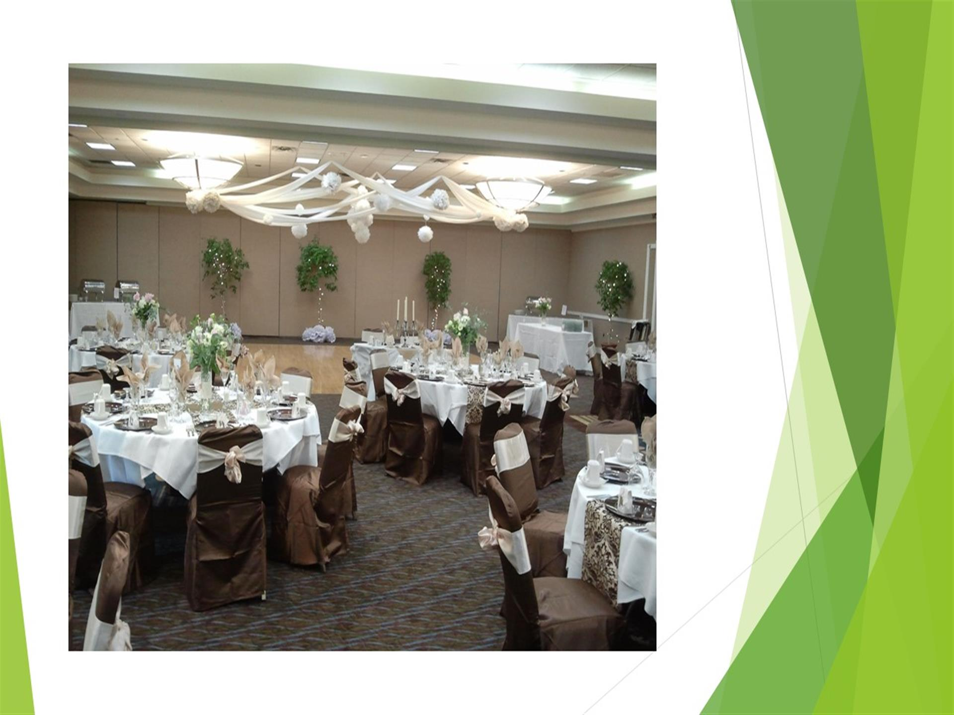 Banquet hall with white tablecloths and brown chairs.