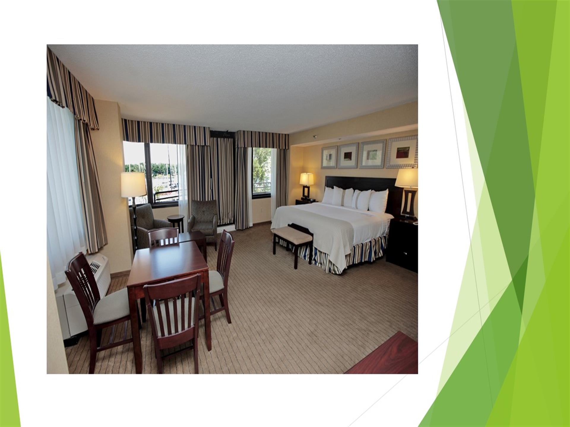 Hotel room showing king size bed, table and chairs, gray carpet, three windows