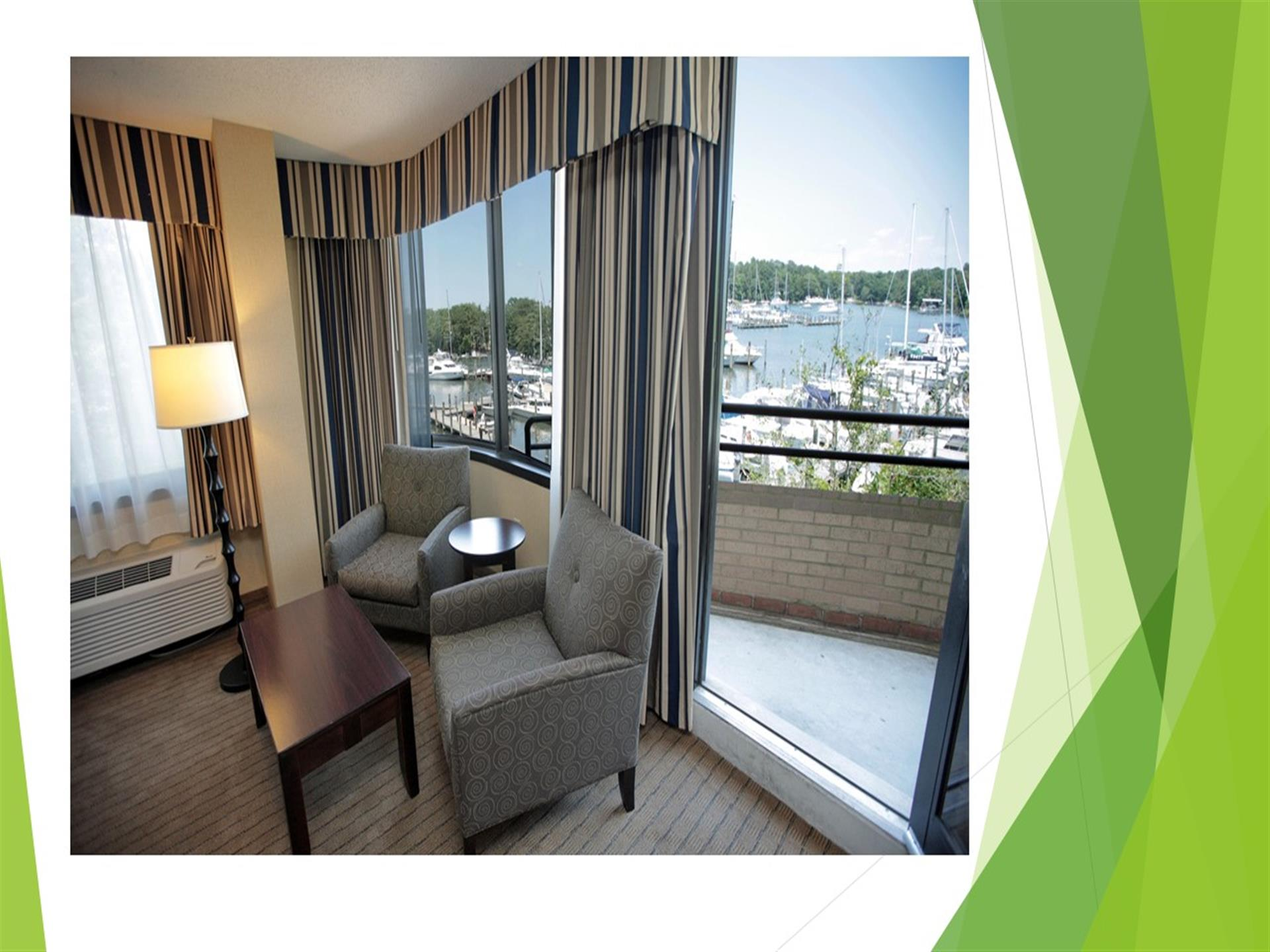 Hotel room with end table, chairs, balcony overlooking harbor