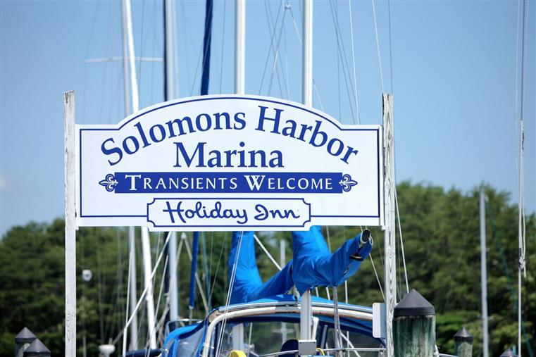 Sign on marina reading Solomons Harbor Marina, Transients Welcome. Holiday Inn