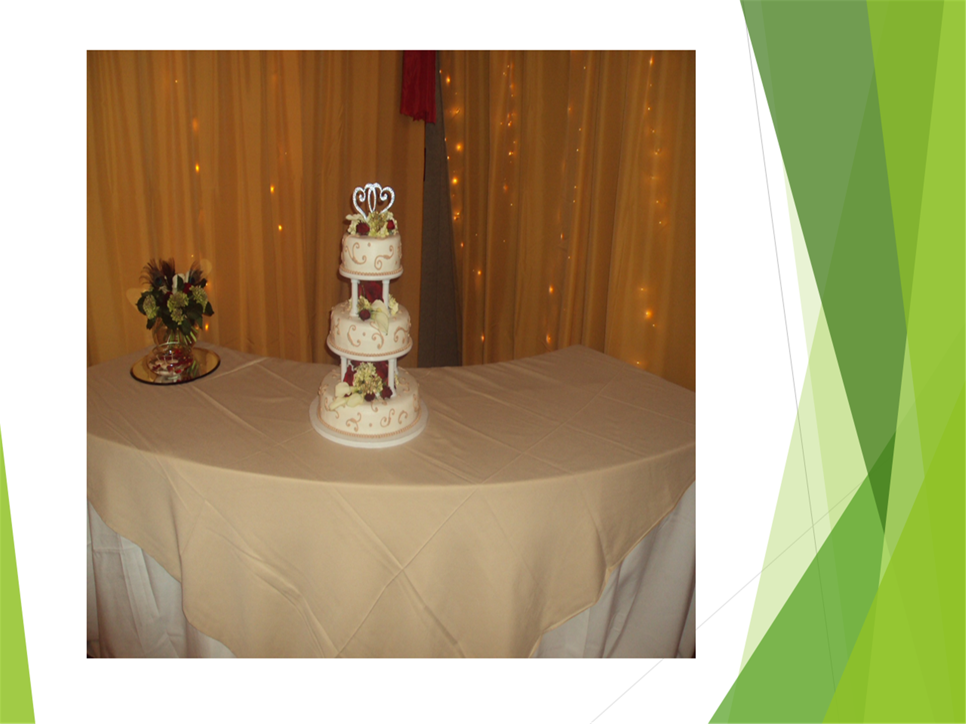 three tier wedding cake on a table with string lights in the background